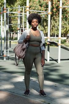 Jonge sportvrouw met handtas die zich op sportterrein bevindt