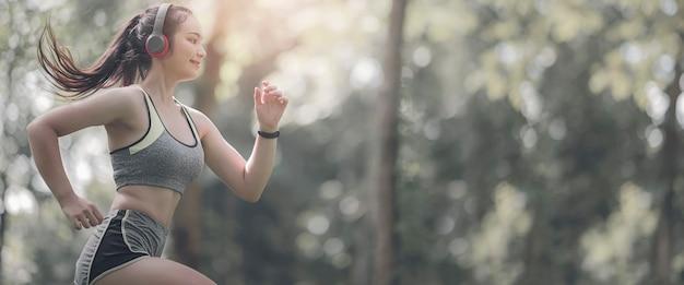 Jonge sportvrouw met hoofdtelefoon die in het park onder het zonlicht loopt. banner voor koptekstontwerp van de website met kopie ruimte.