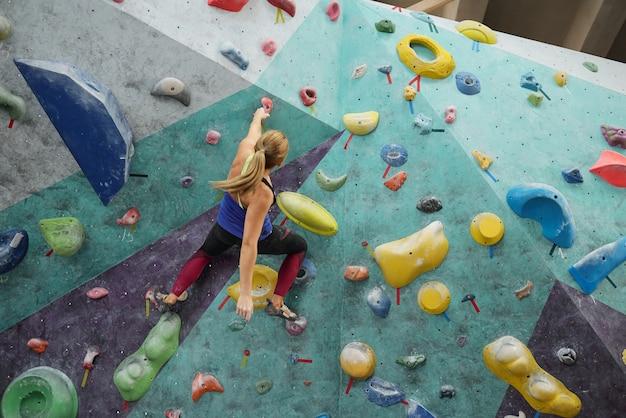 Jonge sportvrouw met paardenstaart houden door een van kunstmatige stenen op klimmuur tijdens het trainen in de sportschool