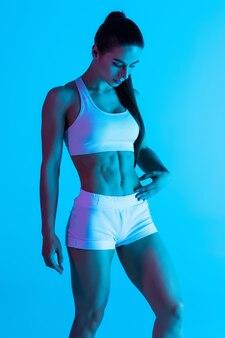 Jonge sportvrouw met perfect lichaam dat op blauwe lichte achtergrond wordt geïsoleerd
