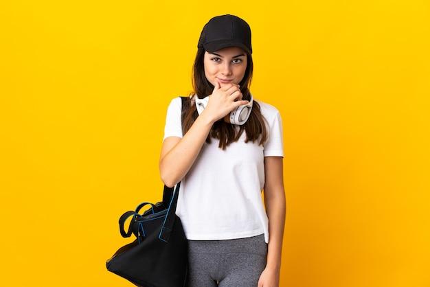 Jonge sportvrouw met sporttas die bij het gele muur denken wordt geïsoleerd