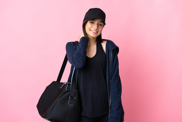 Jonge sportvrouw met sporttas die bij het roze lachen wordt geïsoleerd