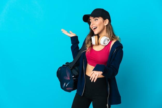 Jonge sportvrouw met sporttas die op blauwe muur met verrassingsuitdrukking wordt geïsoleerd terwijl u kant kijkt Premium Foto