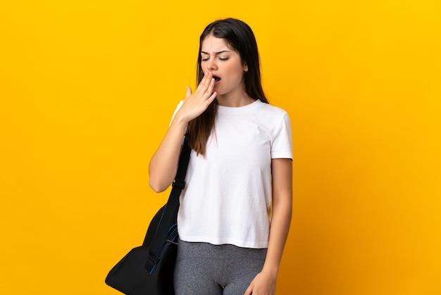 Jonge sportvrouw met sporttas die op geel geeuwen wordt geïsoleerd die en wijd open mond met hand behandelt