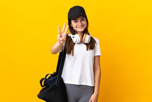 Jonge sportvrouw met sporttas die op gele muur gelukkig wordt geïsoleerd en drie met vingers telt