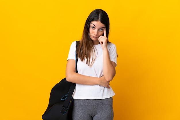 Jonge sportvrouw met sporttas die op gele muur wordt geïsoleerd die een idee denkt