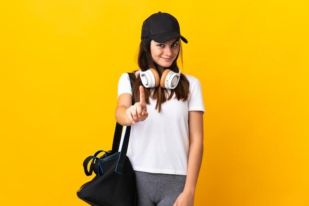 Jonge sportvrouw met sporttas die op gele muur wordt geïsoleerd die en een vinger toont opheft