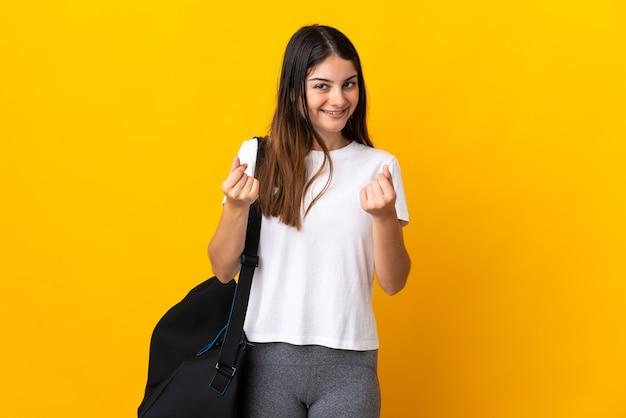 Jonge sportvrouw met sporttas die op gele muur wordt geïsoleerd die geldgebaar maakt