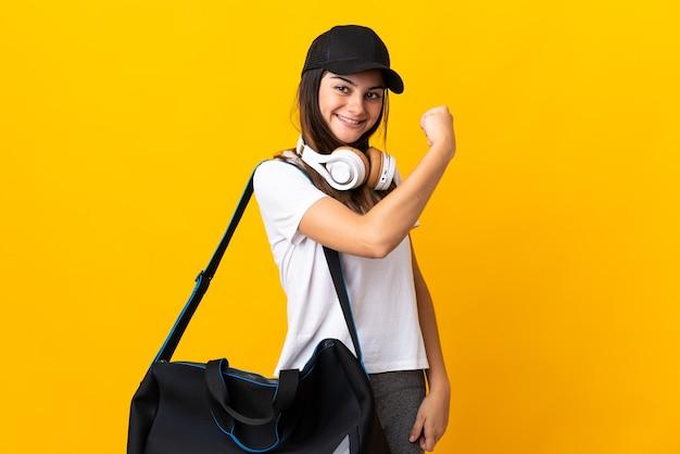 Jonge sportvrouw met sporttas die op gele muur wordt geïsoleerd die sterk gebaar doet