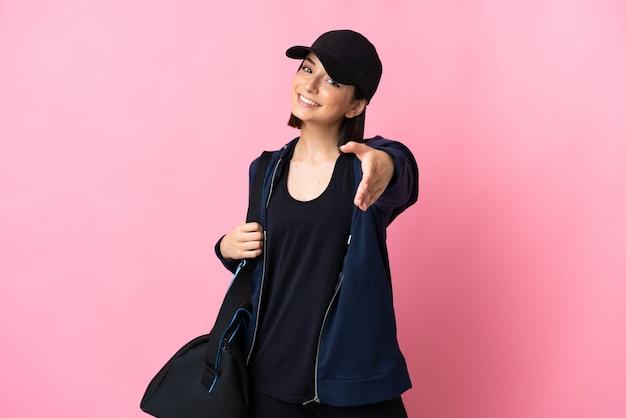 Jonge sportvrouw met sporttas die op roze achtergrond wordt geïsoleerd die handen schudden voor het sluiten van een goede deal