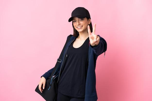 Jonge sportvrouw met sporttas die op roze wordt geïsoleerd die en overwinningsteken glimlacht toont