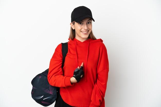 Jonge sportvrouw met sporttas die op witte achtergrond met verrassingsgelaatsuitdrukking wordt geïsoleerd