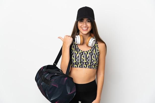 Jonge sportvrouw met sporttas die op witte achtergrond wordt geïsoleerd die naar de kant wijst om een product te presenteren