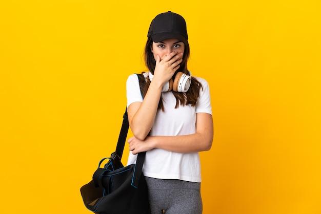 Jonge sportvrouw met sporttas geïsoleerd op geel verrast en geschokt terwijl ze naar rechts kijkt