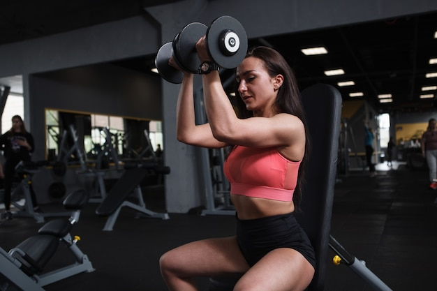 Jonge sportvrouw met sterke armen trainen met halters in de sportschool, kopieer ruimte