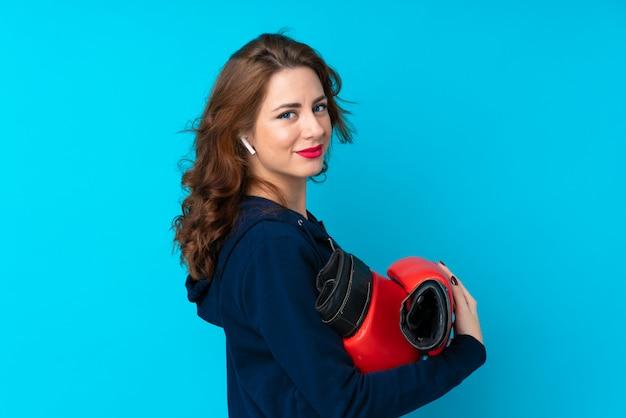 Jonge sportvrouw over geïsoleerd blauw met bokshandschoenen