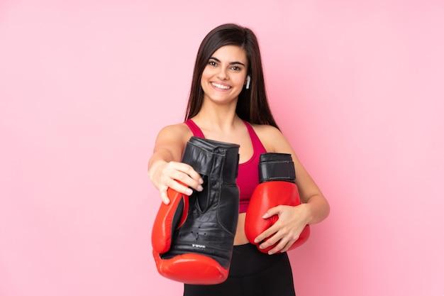 Jonge sportvrouw over geïsoleerd roze met bokshandschoenen