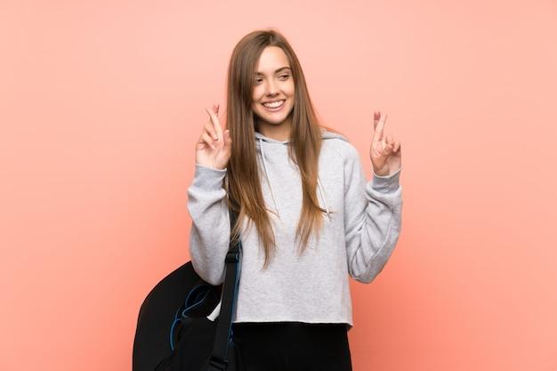 Jonge sportvrouw over geïsoleerd roze met vingers kruising