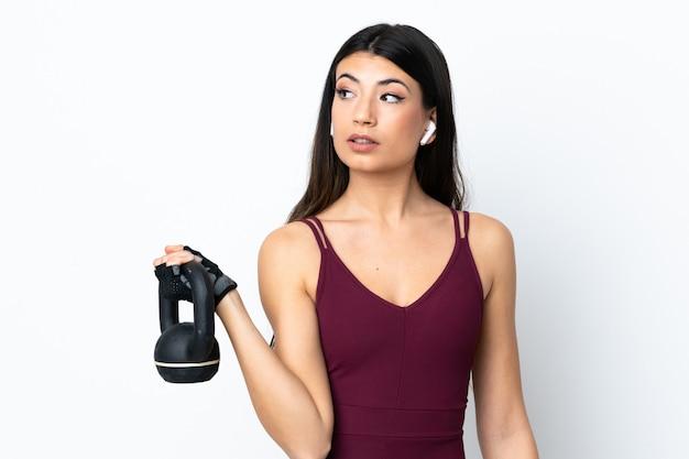 Jonge sportvrouw over geïsoleerd wit die gewichtheffen met kettlebell maken