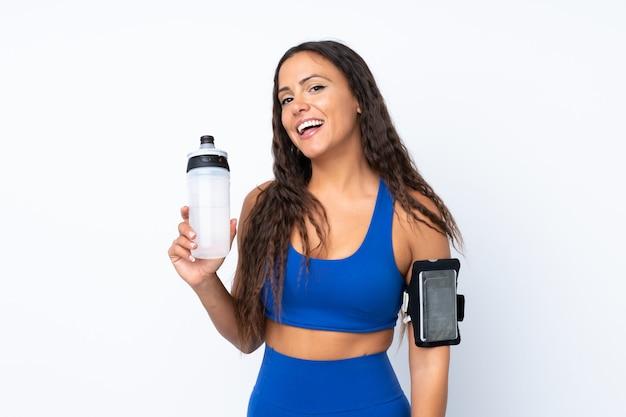 Jonge sportvrouw over geïsoleerd wit met de fles van het sportenwater