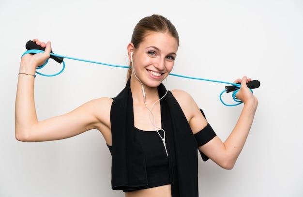 Jonge sportvrouw over geïsoleerd wit met touwtjespringen