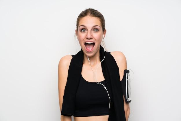 Jonge sportvrouw over geïsoleerd wit met verrassingsgelaatsuitdrukking