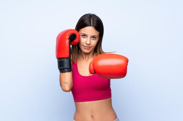Jonge sportvrouw over geïsoleerde blauwe muur met bokshandschoenen