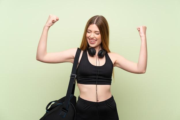 Jonge sportvrouw over geïsoleerde groen vierend een overwinning