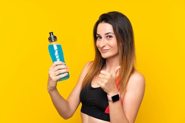 Jonge sportvrouw over geïsoleerde muur met een fles soda
