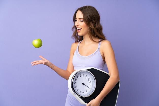 Jonge sportvrouw over geïsoleerde purpere muur met weegmachine en met een appel