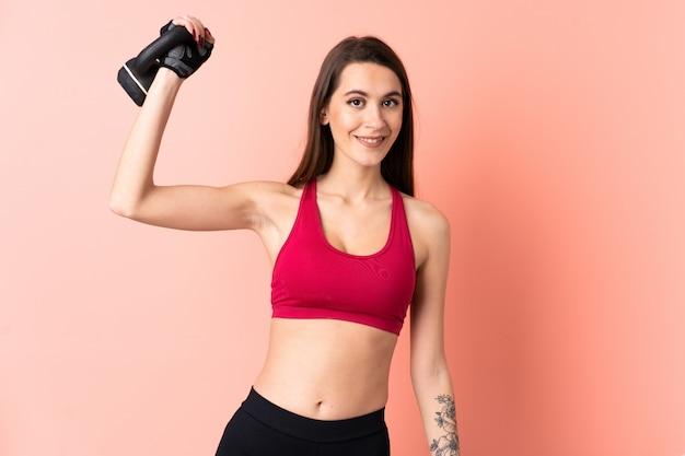 Jonge sportvrouw over geïsoleerde roze muur die gewichtheffen met kettlebell maakt