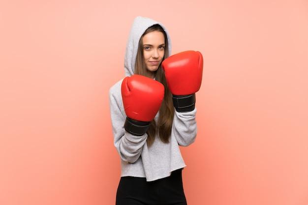 Jonge sportvrouw over geïsoleerde roze muur met bokshandschoenen