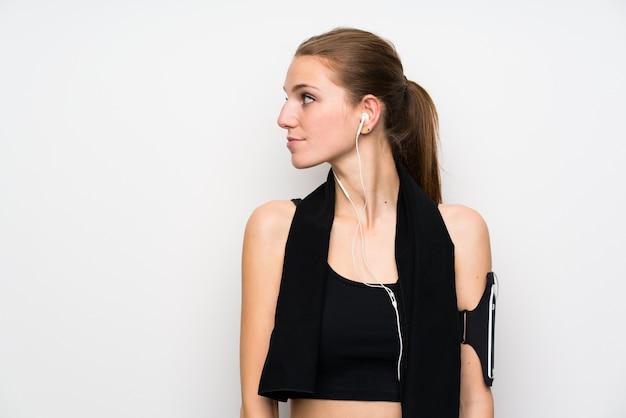 Jonge sportvrouw over geïsoleerde witte en muur die zich bevindt kijkt