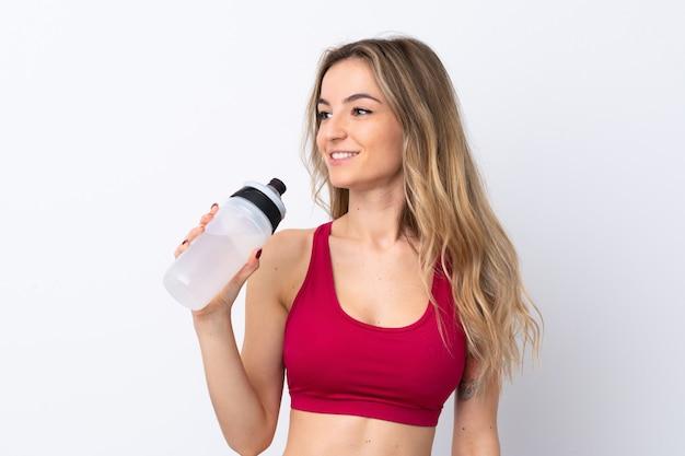 Jonge sportvrouw over geïsoleerde witte muur met de fles van het sportenwater