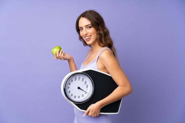Jonge sportvrouw over purpere muur met wegende machine en met een appel