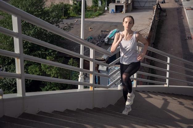 Jonge sportvrouw rent actief de trap op