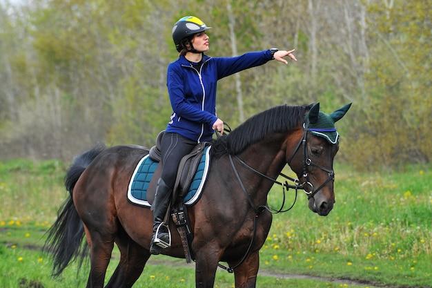 Jonge sportvrouw rijdt paard