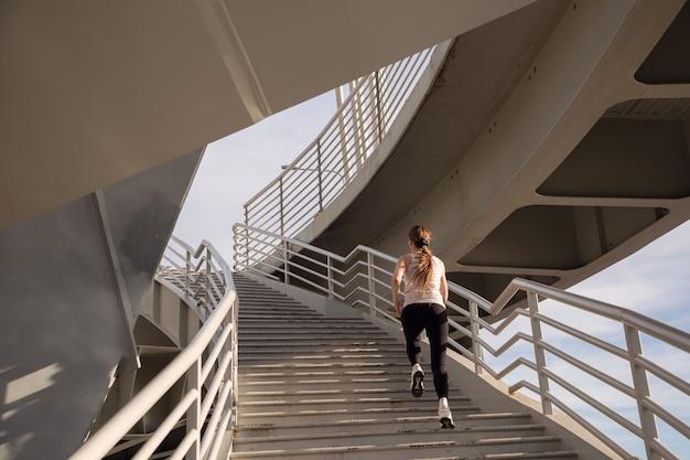 Jonge sportvrouw traplopen bij zonsondergang