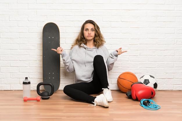 Jonge sportvrouw zittend op de vloer wijzend op de zijkanten met twijfels