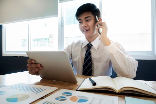 Jonge startende bedrijfsberoeps die aan een cliënt op zijn cellphone spreekt.