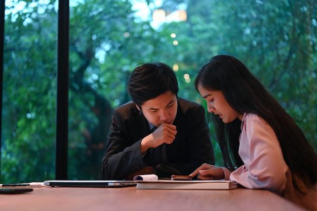 Jonge startende bedrijfsmensen die businessplan bespreken bij vergaderzaal.