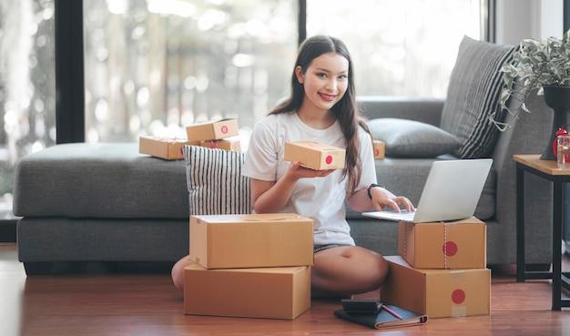Jonge startonderneemster die thuis, glimlachend en kijkt werkt