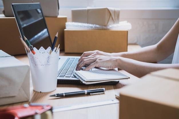 Jonge startup kleine bedrijfsondernemersvrouw die met slimme telefoon thuis werken