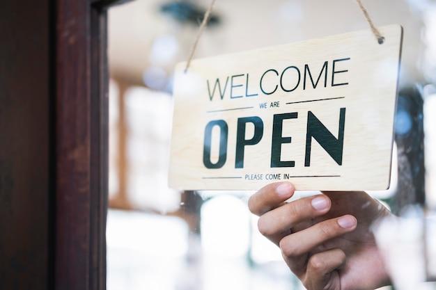 Jonge startup koffie cafe owener open en welkom klant.
