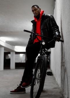 Jonge stedelijke man lopen met zijn fiets