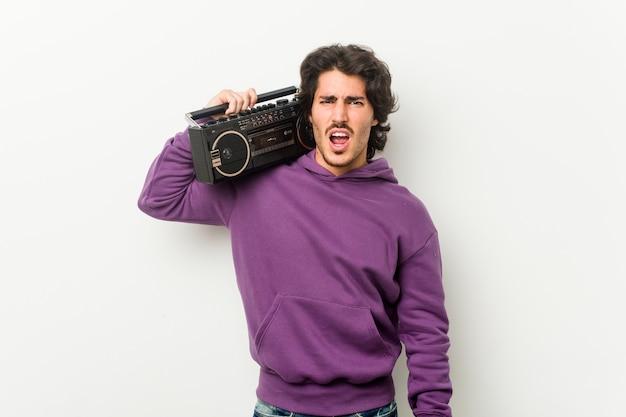 Jonge stedelijke man met een guettoblaster die erg boos en agressief schreeuwt
