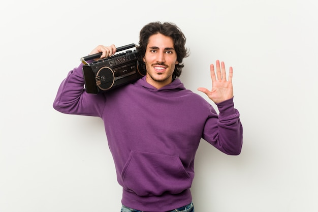 Jonge stedelijke mens die een guettoblaster houden die vrolijk tonend nummer vijf met vingers glimlachen.