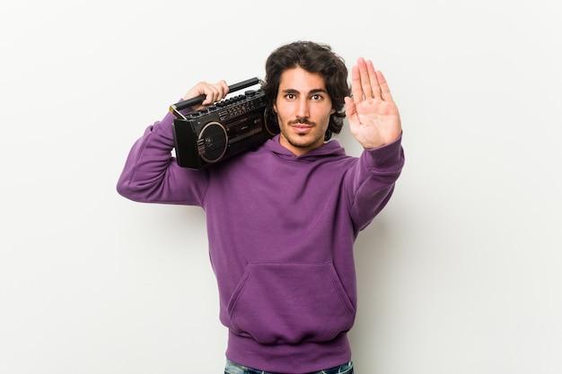 Jonge stedelijke mens die een guettoblaster houdt die zich met uitgestrekte hand bevindt die eindeteken toont