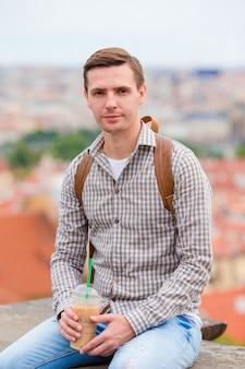Jonge stedelijke mens het drinken koffie europese stad als achtergrond in openlucht
