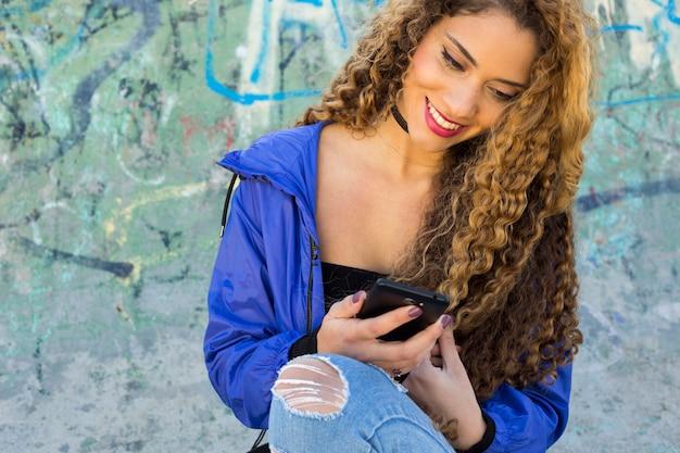 Jonge stedelijke vrouw voor graffitimuur